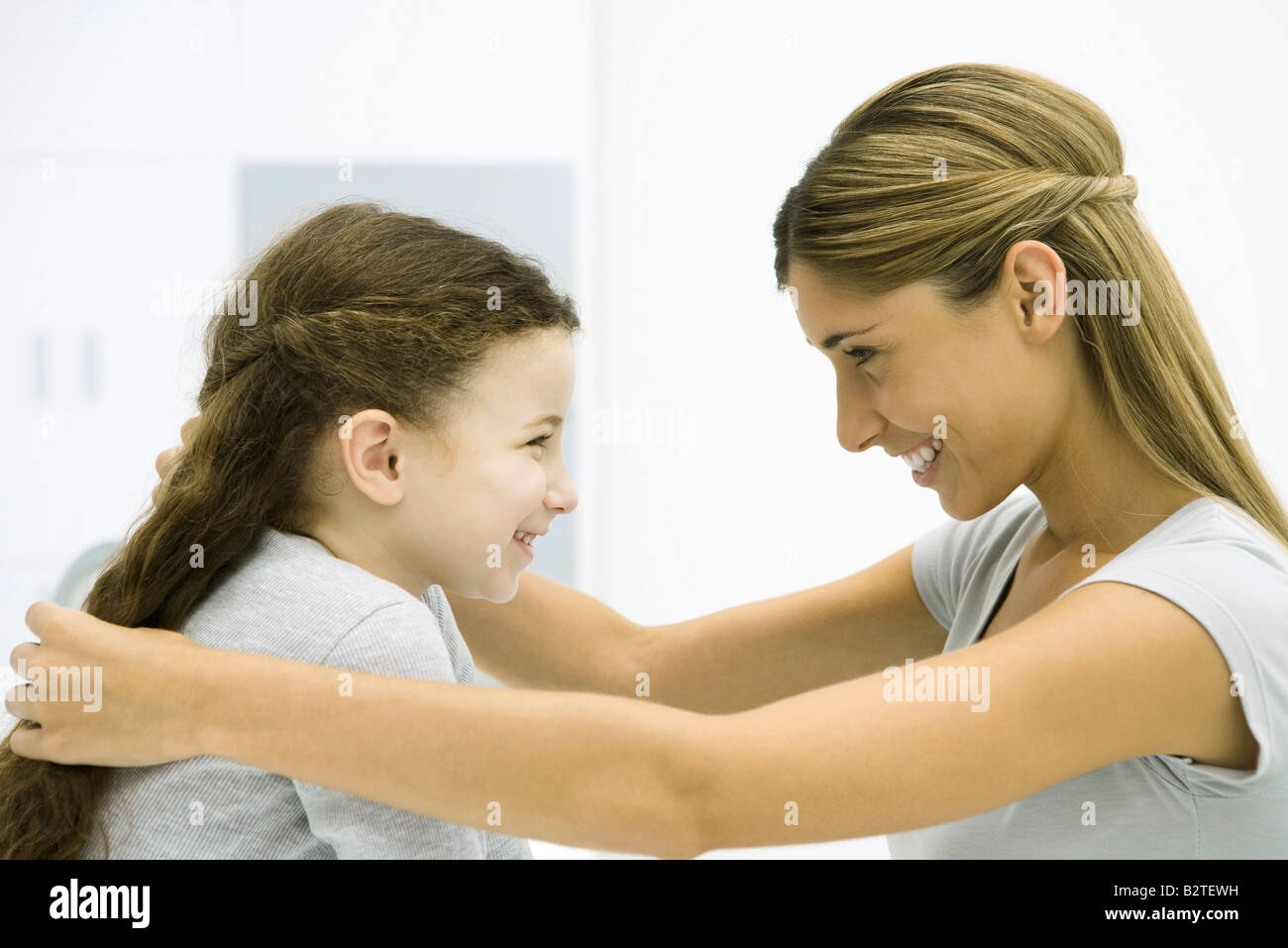 Mother and daughter face to face, smiling, woman touching girl's hair - Stock Image