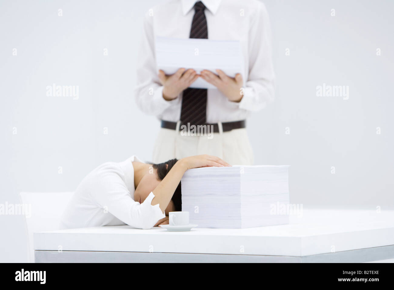 Woman with head down on desk, next to tall stack of papers, man holding another stack of paper - Stock Image