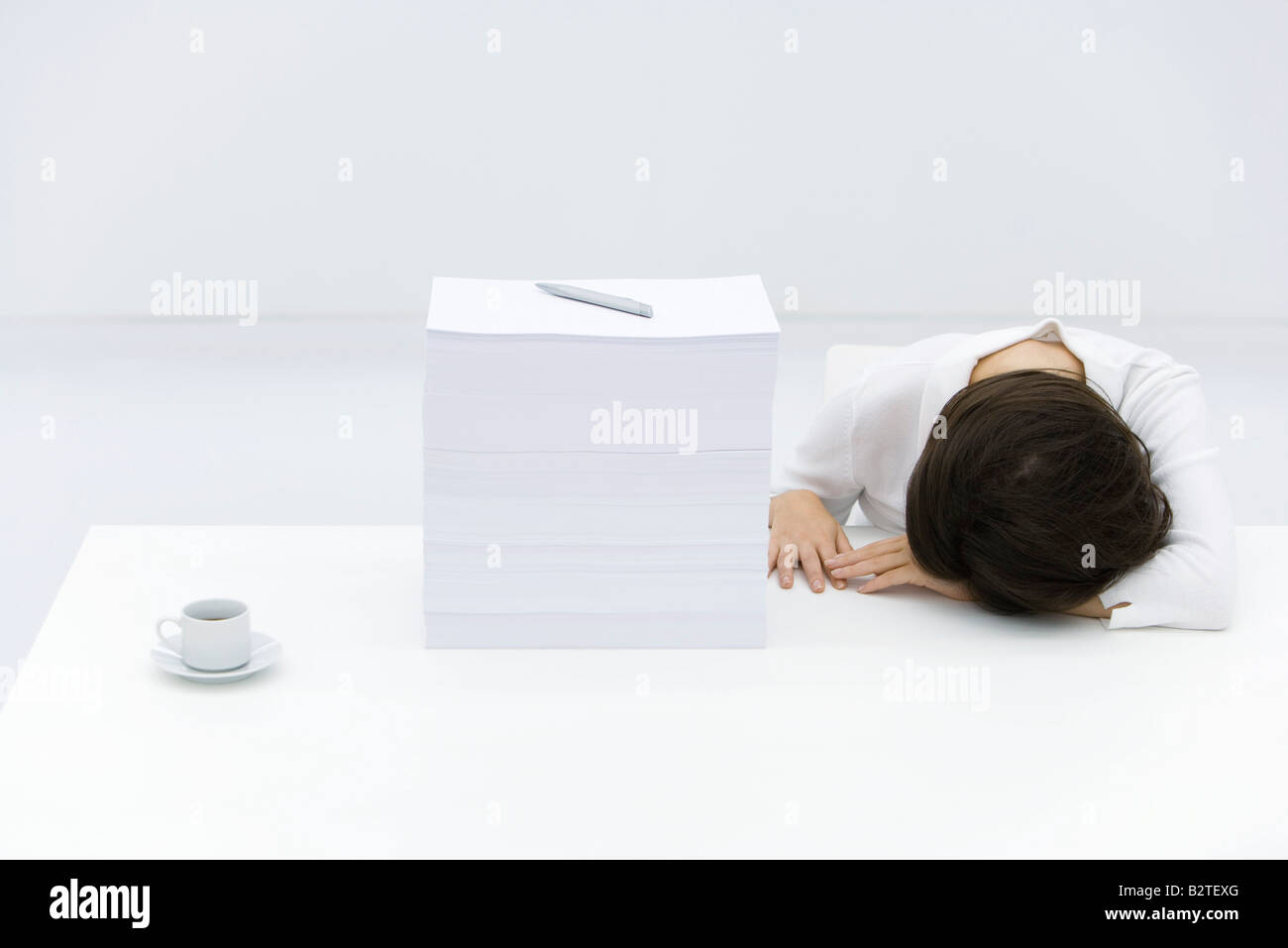 Woman with head down on desk, next to tall stack of papers - Stock Image