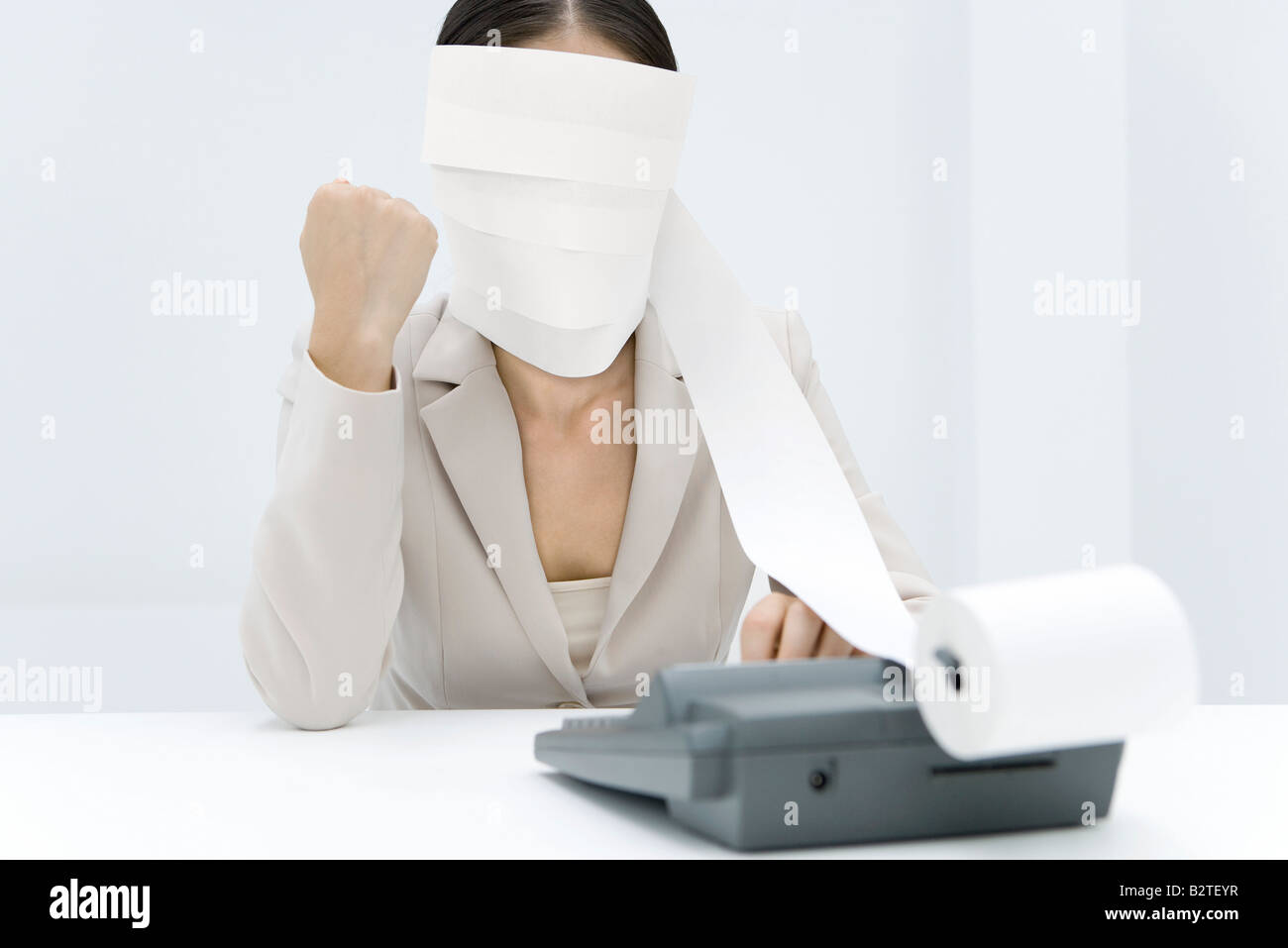 Woman sitting at desk, tape from an adding machine wrapped around her head, clenching fist - Stock Image