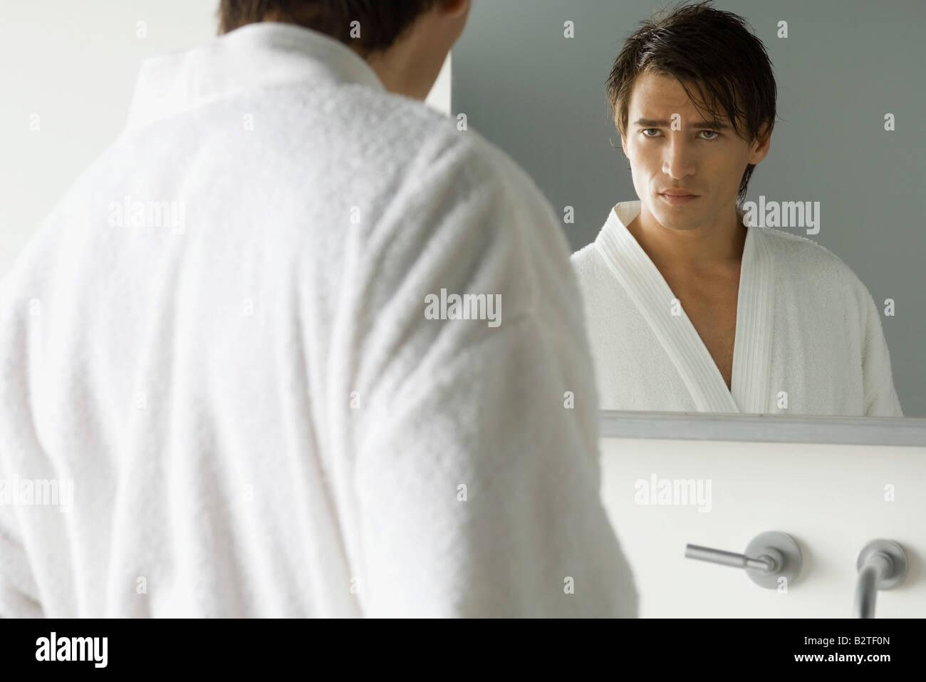 Man looking at himself in mirror, wearing bathrobe, furrowing brow - Stock Image