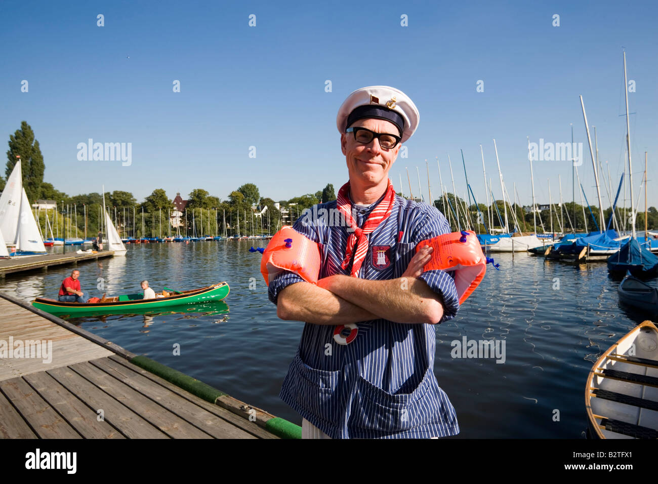 Fisher smiling at camera, Man wearing a Fischerhemd a typical shirt of a fisher, water wings and a sailor's - Stock Image