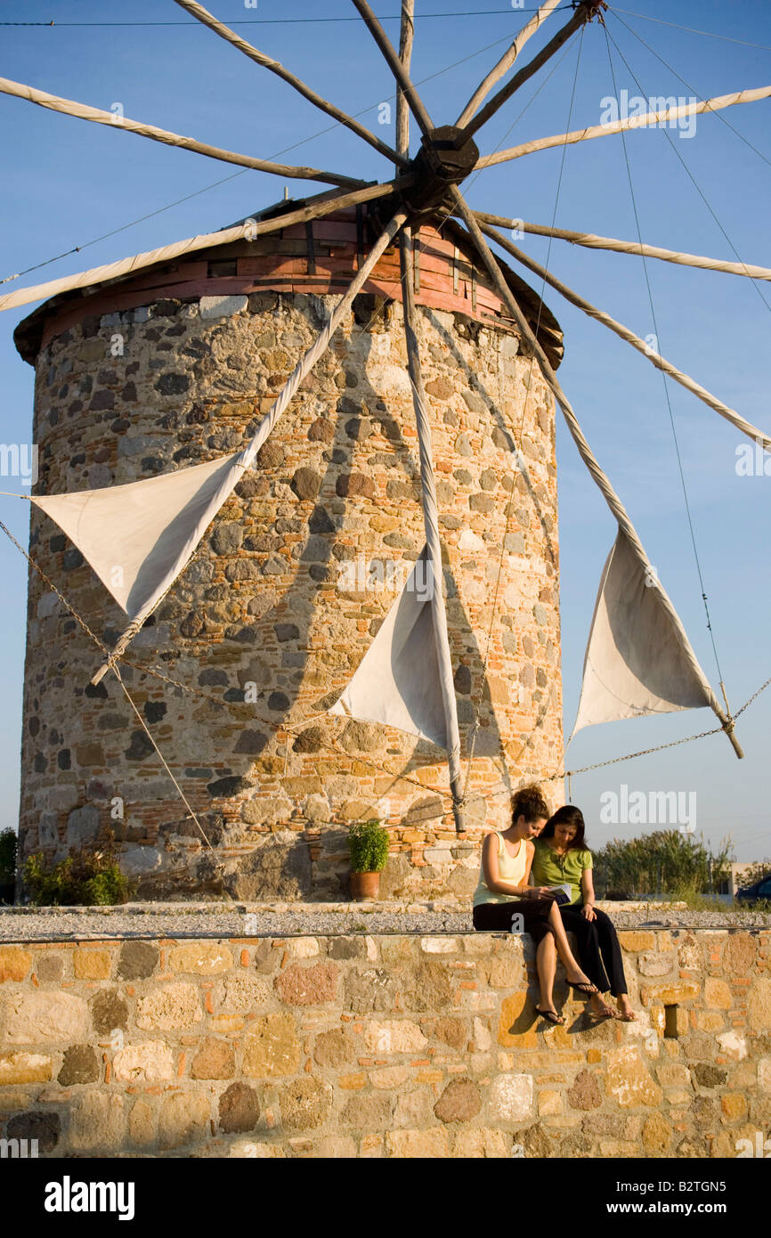 Two women sitting in front of a windmill and reading a book, Antimachia, Kos, Greece - Stock Image