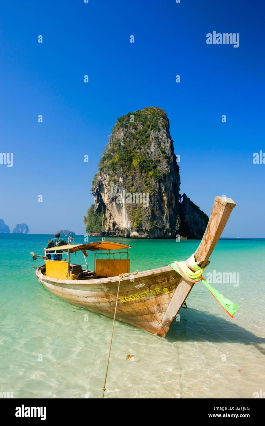 Anchored boat, chalk cliff in background, Phra Nang Beach, Laem Phra Nang, Railay, Krabi, Thailand - Stock Image
