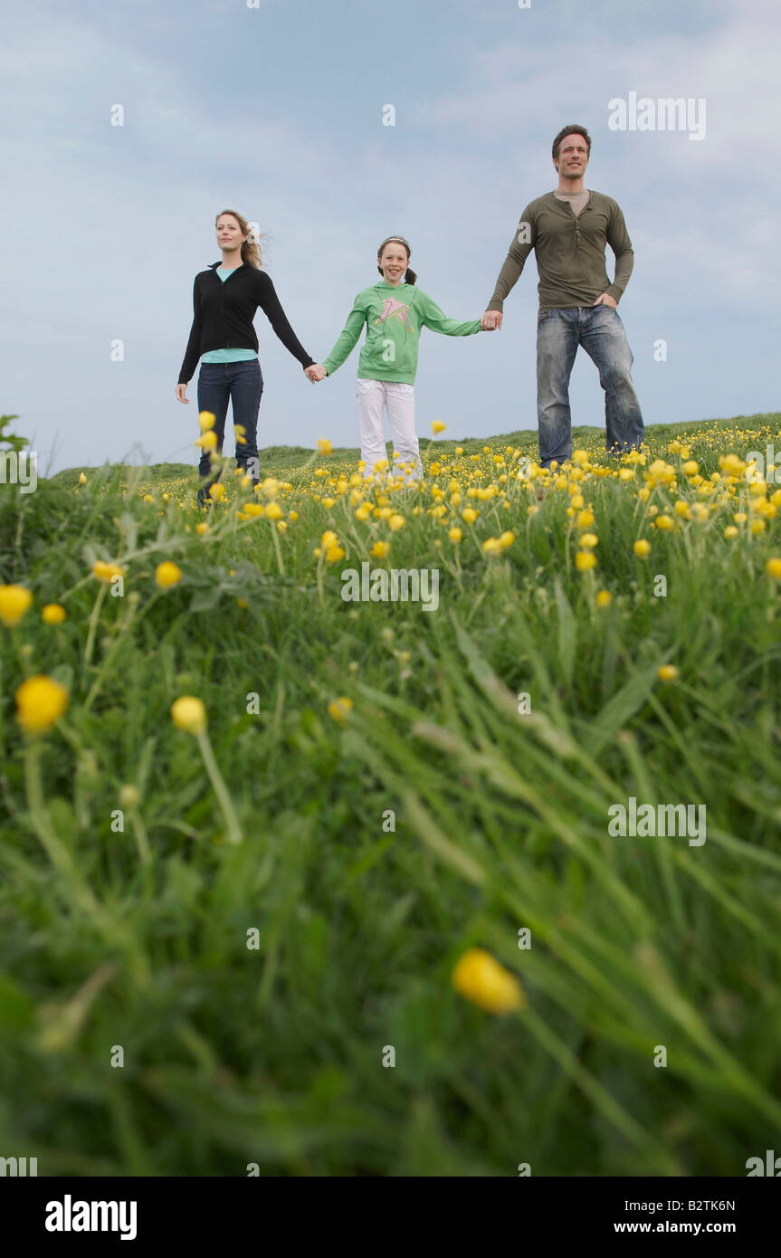 Parents and child stand on hillside Stock Photo