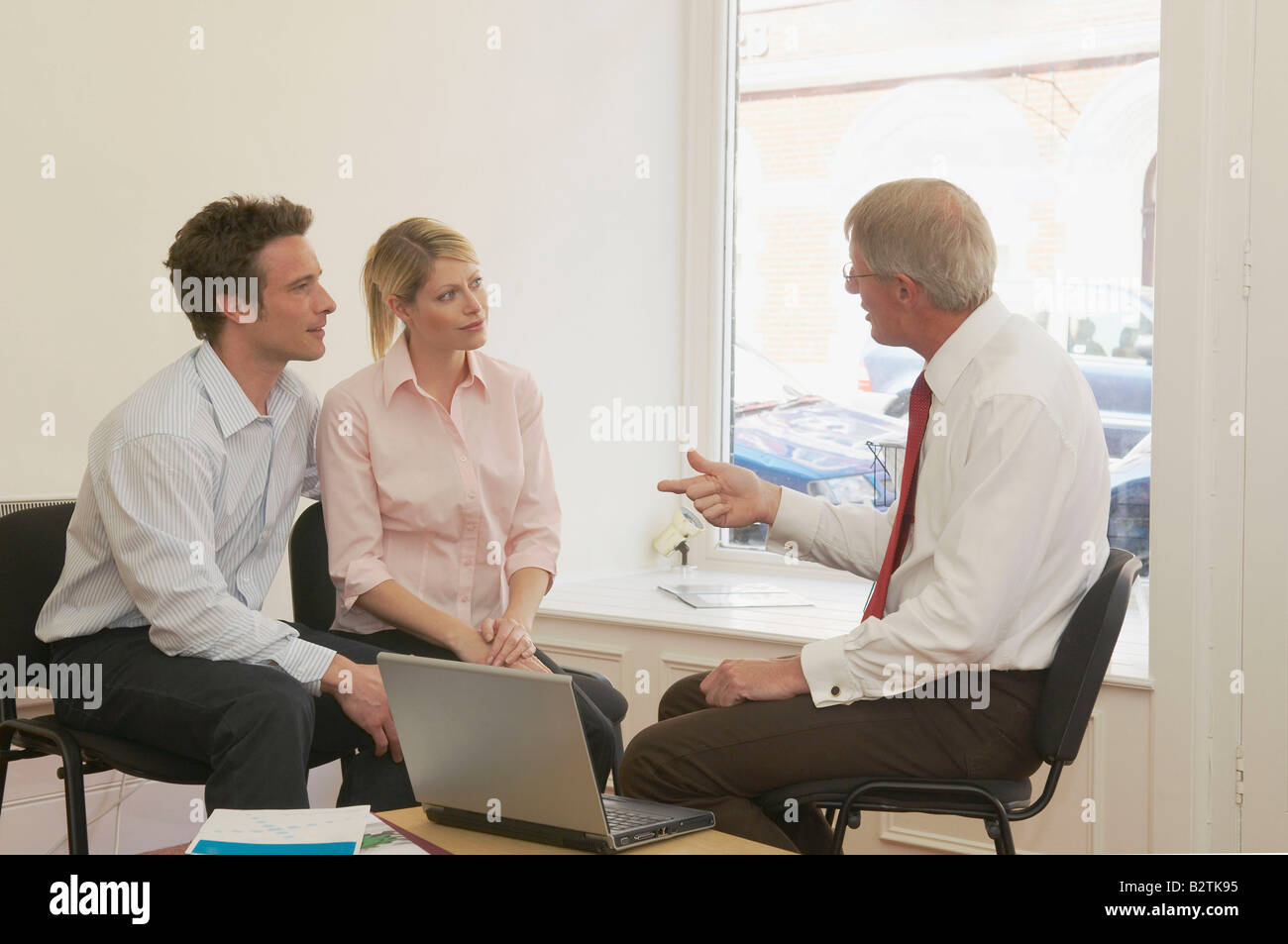 Couple in talks with financial advisor - Stock Image
