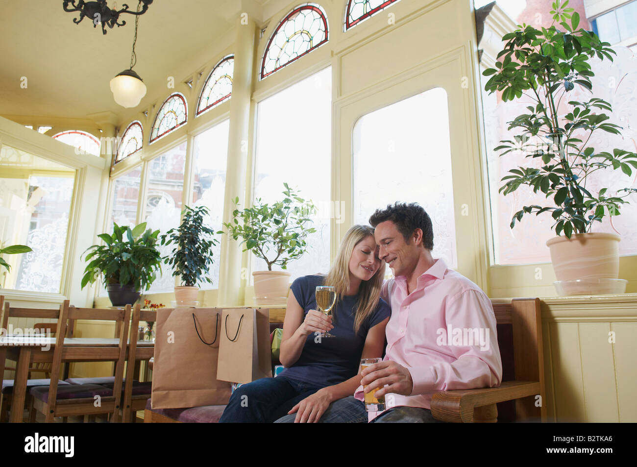 Couple relax in pub after shopping - Stock Image