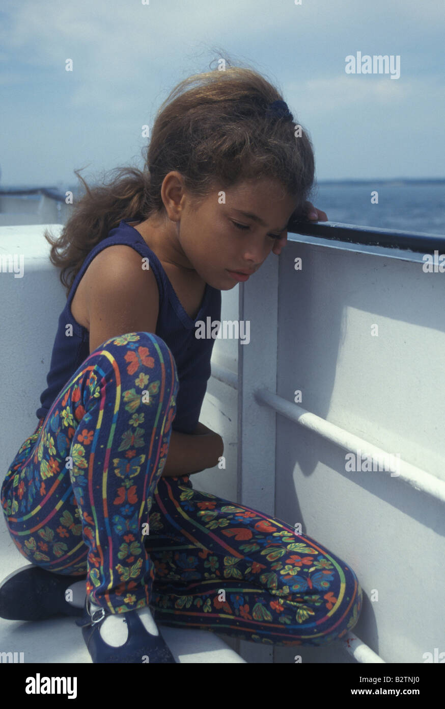 little girl crouched on the deck of a ferry feeling sea sick - Stock Image
