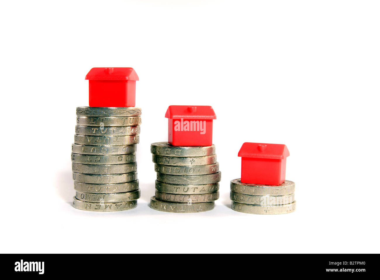 Small red model houses stacked on top of piles of coins isolated objects Property ladder Housing market credit crunch - Stock Image