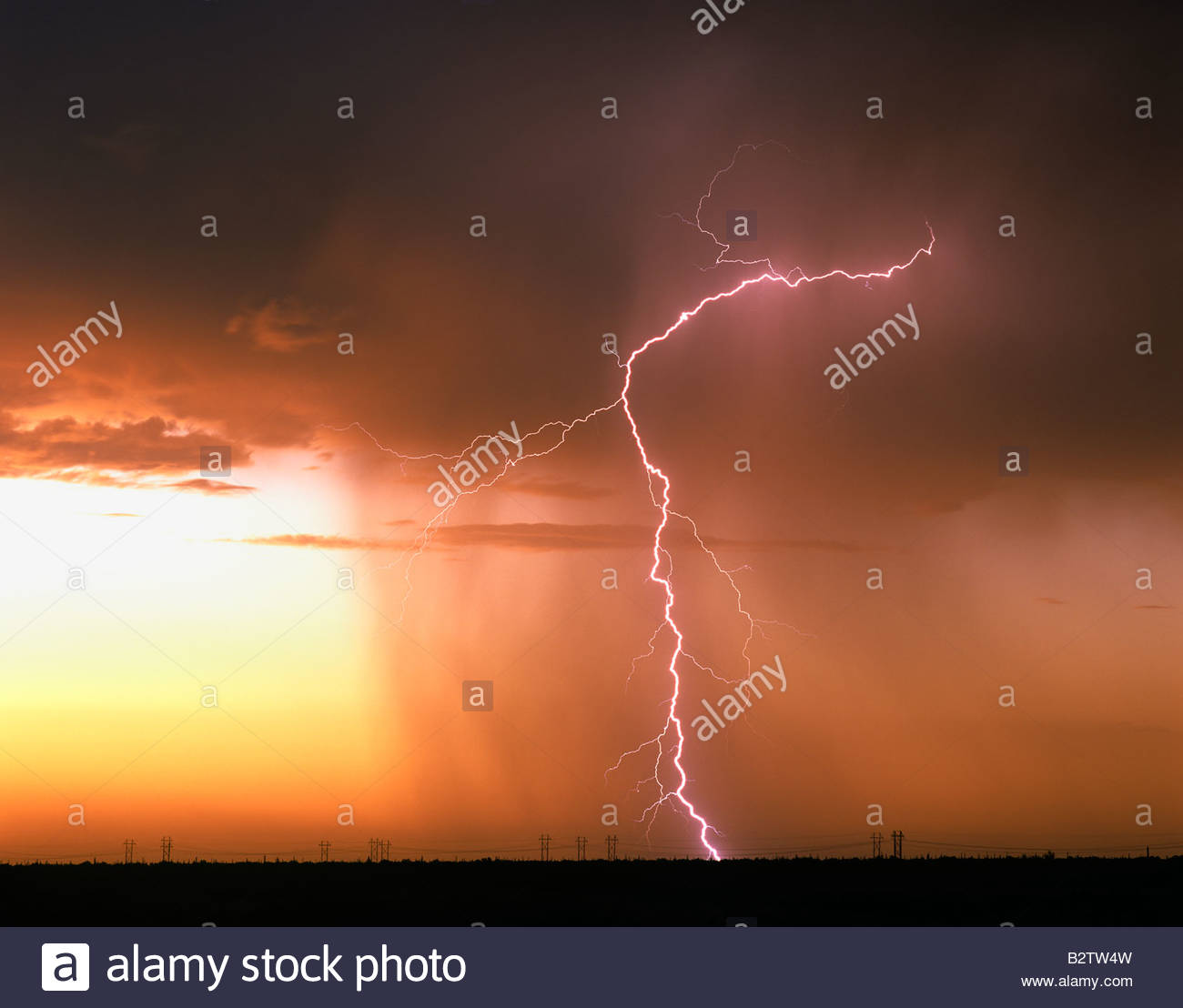 Thunderbolt at sunset with rain North East of Marana Arizona a row of power transmission lines down bellow - Stock Image
