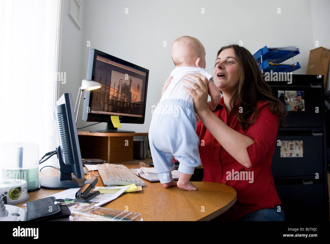 home office multitasking. Multitasking Woman Working Mother Juggles Work In Home Office And Looking After Baby Standing On Her Desk I