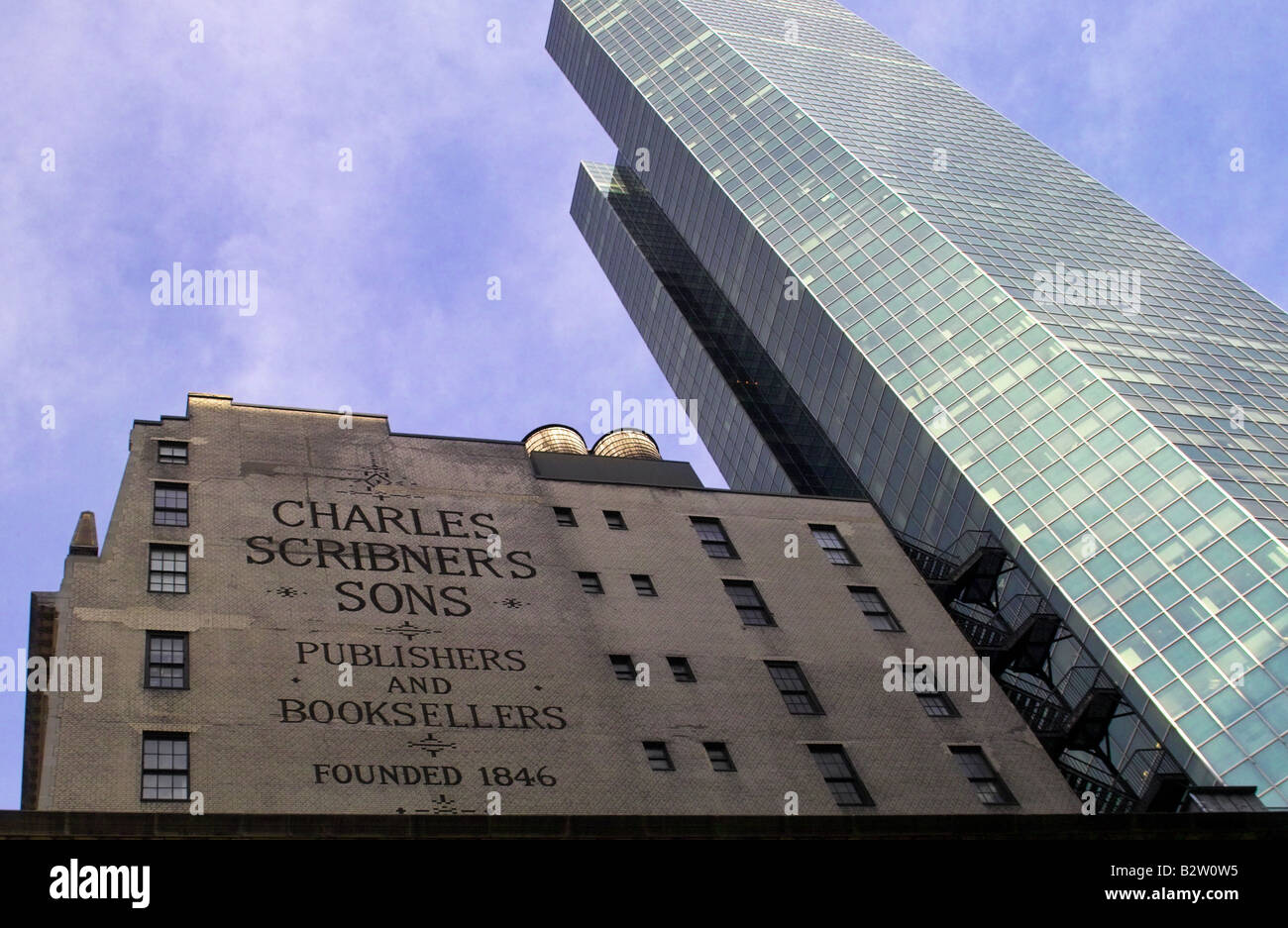 Charles Scribner's old office building dwarfed by modern sky scrapper, New York - Stock Image