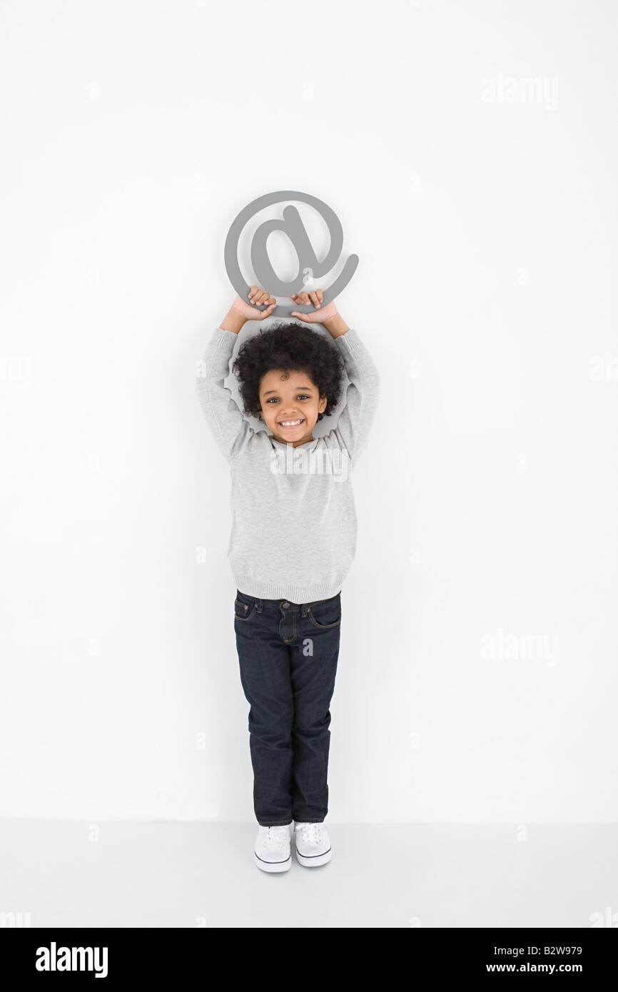 Boy holding an at symbol - Stock Image