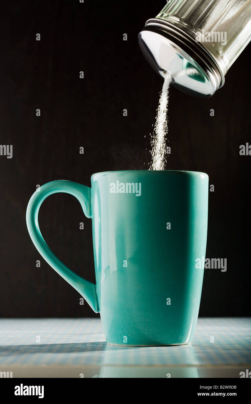 Pouring sugar into a coffee cup - Stock Image
