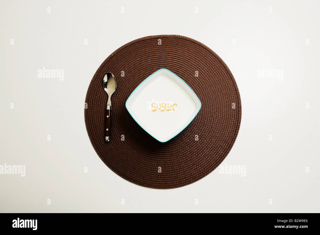 Bowl of sugar and spoon - Stock Image