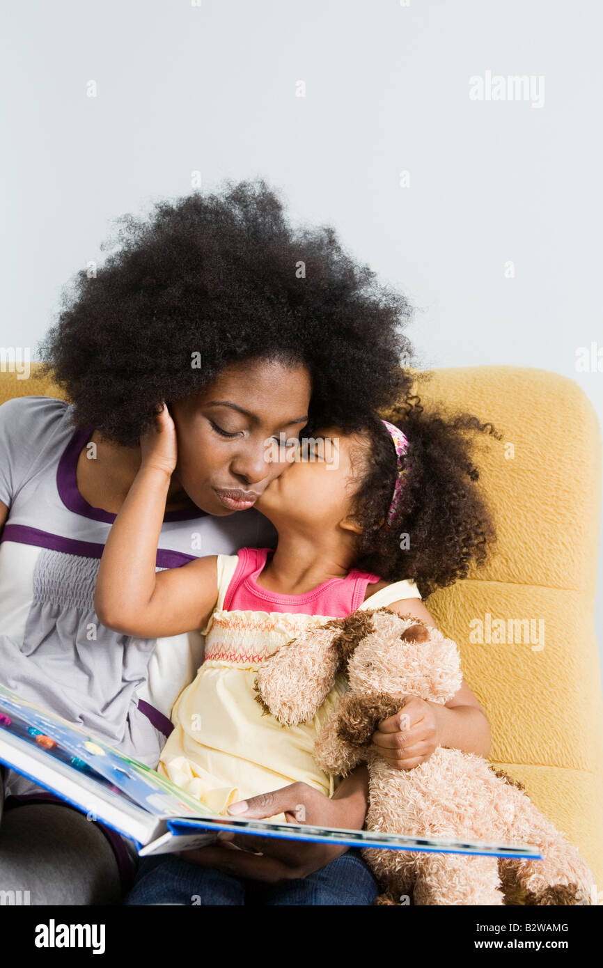 A girl kissing her mother on the cheek Stock Photo