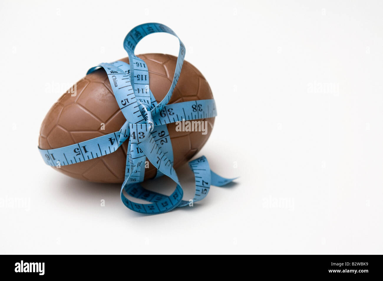 A tape measure tied round an easter egg - Stock Image