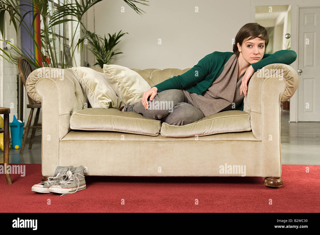 Sullen young woman on sofa - Stock Image