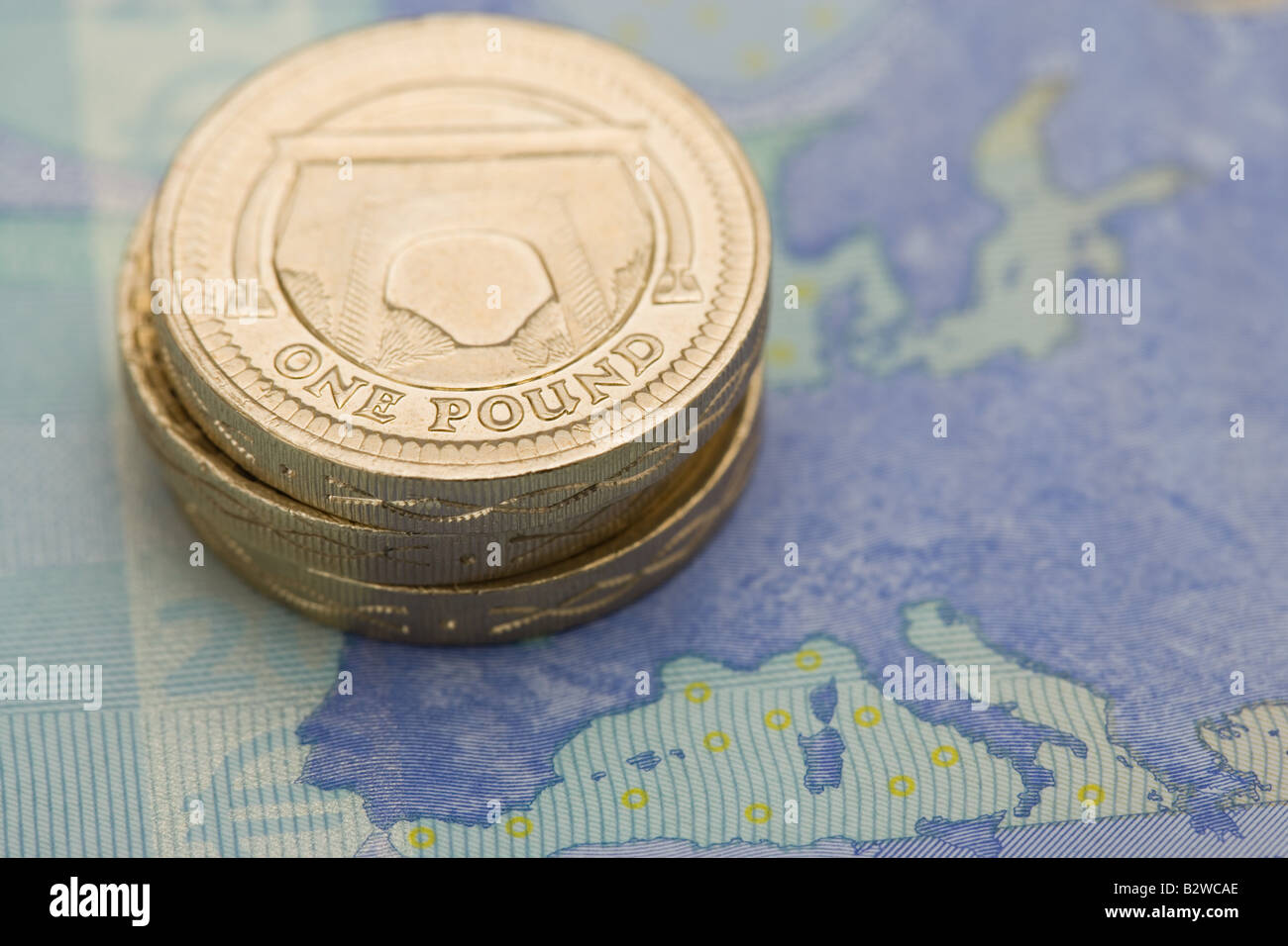 Pound coins on euro note Stock Photo