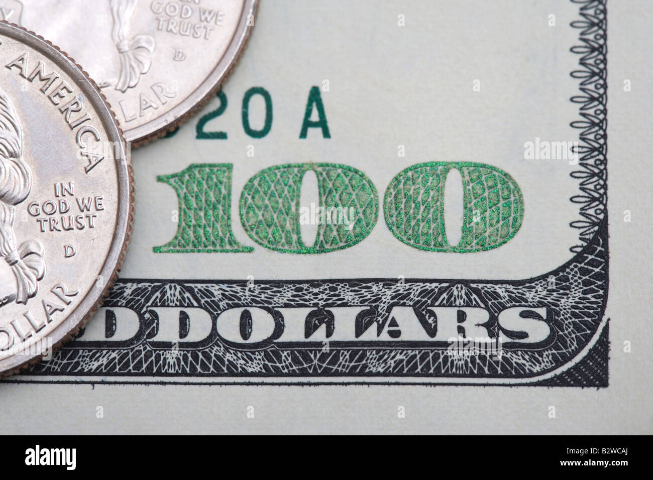 Quarters on one hundred dollar bill - Stock Image