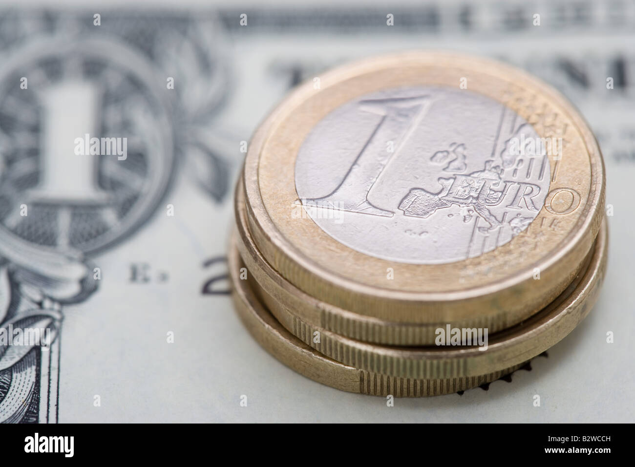 Euro coins on dollar bill - Stock Image