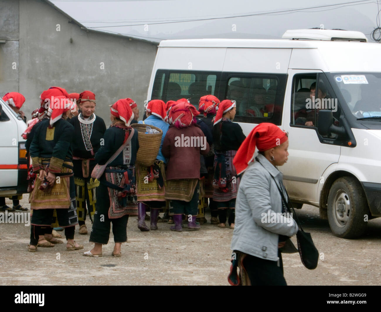 Red Dzao hilltribe women clamour round tourists and tourist buses to sell handicrafts Ta Phin village near Sapa Stock Photo