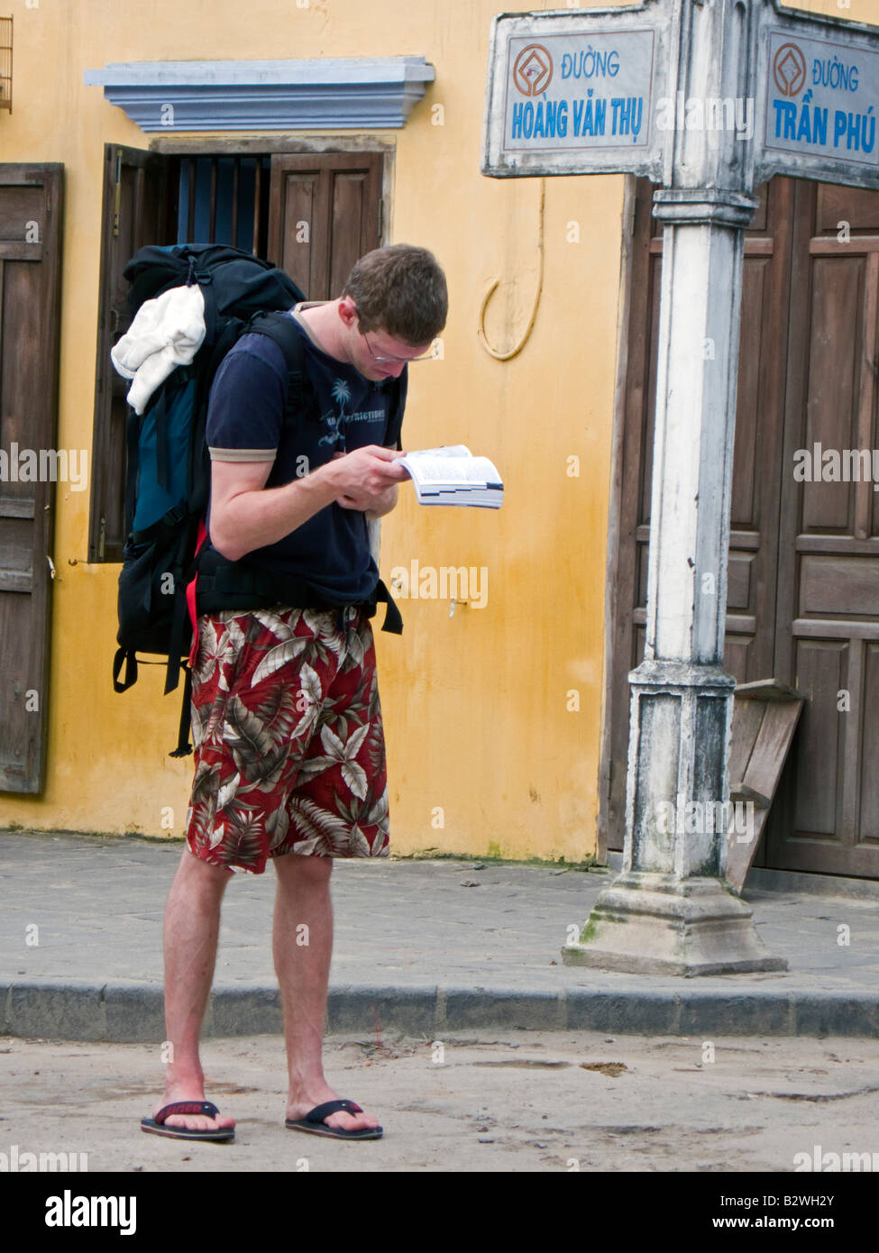 Young male backpacker consults Lonely Planet guide Hoi An Vietnam Stock Photo