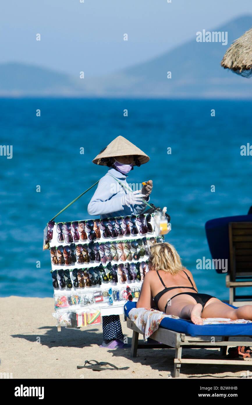 Conical hat woman selling sunglasses on beach Nha Trang resort Vietnam - Stock Image