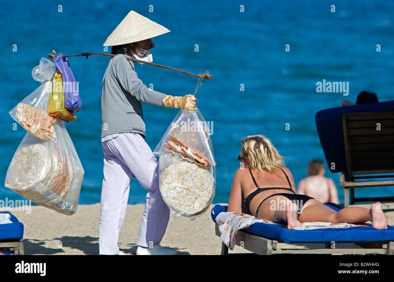 Conical hat woman selling snacks on beach Nha Trang resort Vietnam - Stock Image