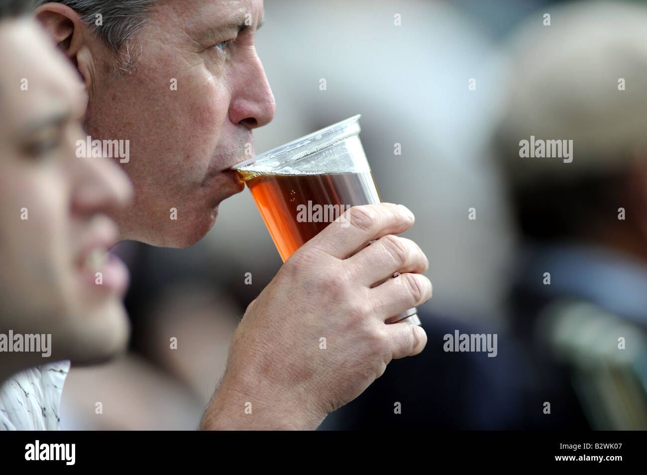 Man sips a pint of beer while watching cricket at the picturesque Arundel ground July 2008 - Stock Image