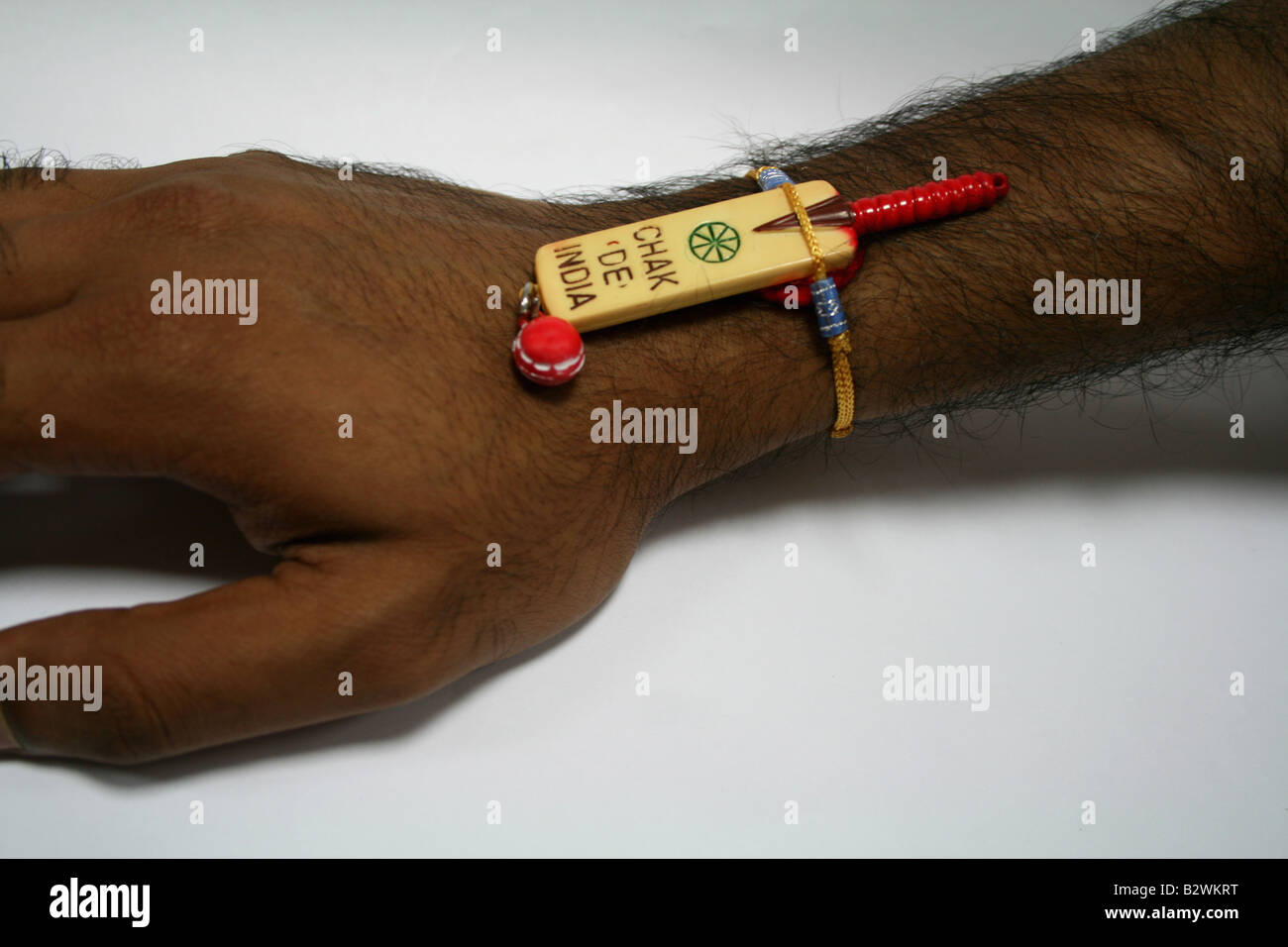 Cricket bat and ball tied to an Indian's hand on popular Indian festival raksha bandhan Stock Photo