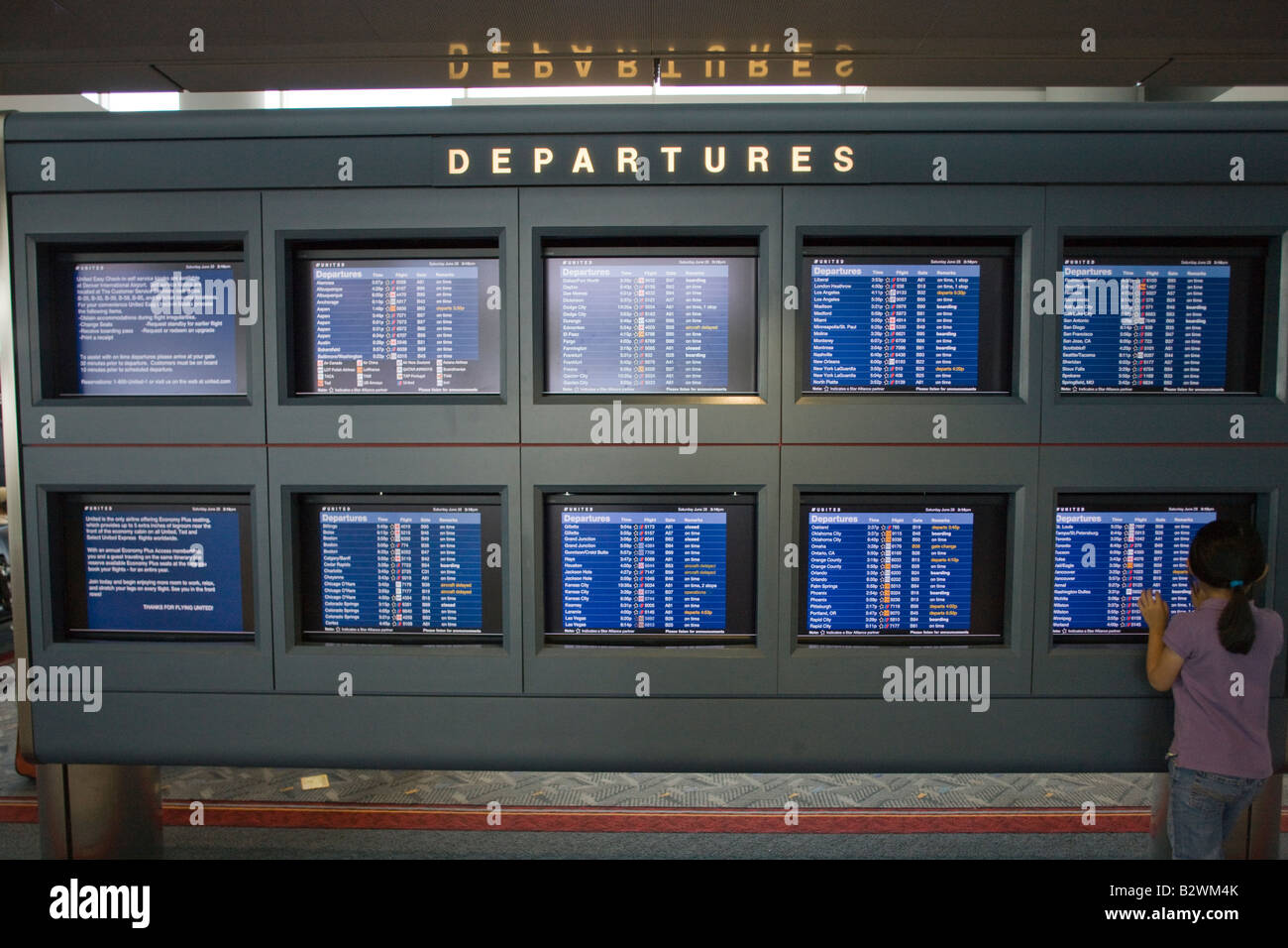 girl looking at flight schedule video terminals, Denver International Airport, Colorado, USA - Stock Image