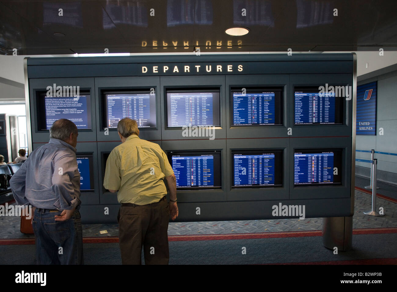 passengers looking at flight schedule video terminals, Denver International Airport, Colorado, USA - Stock Image