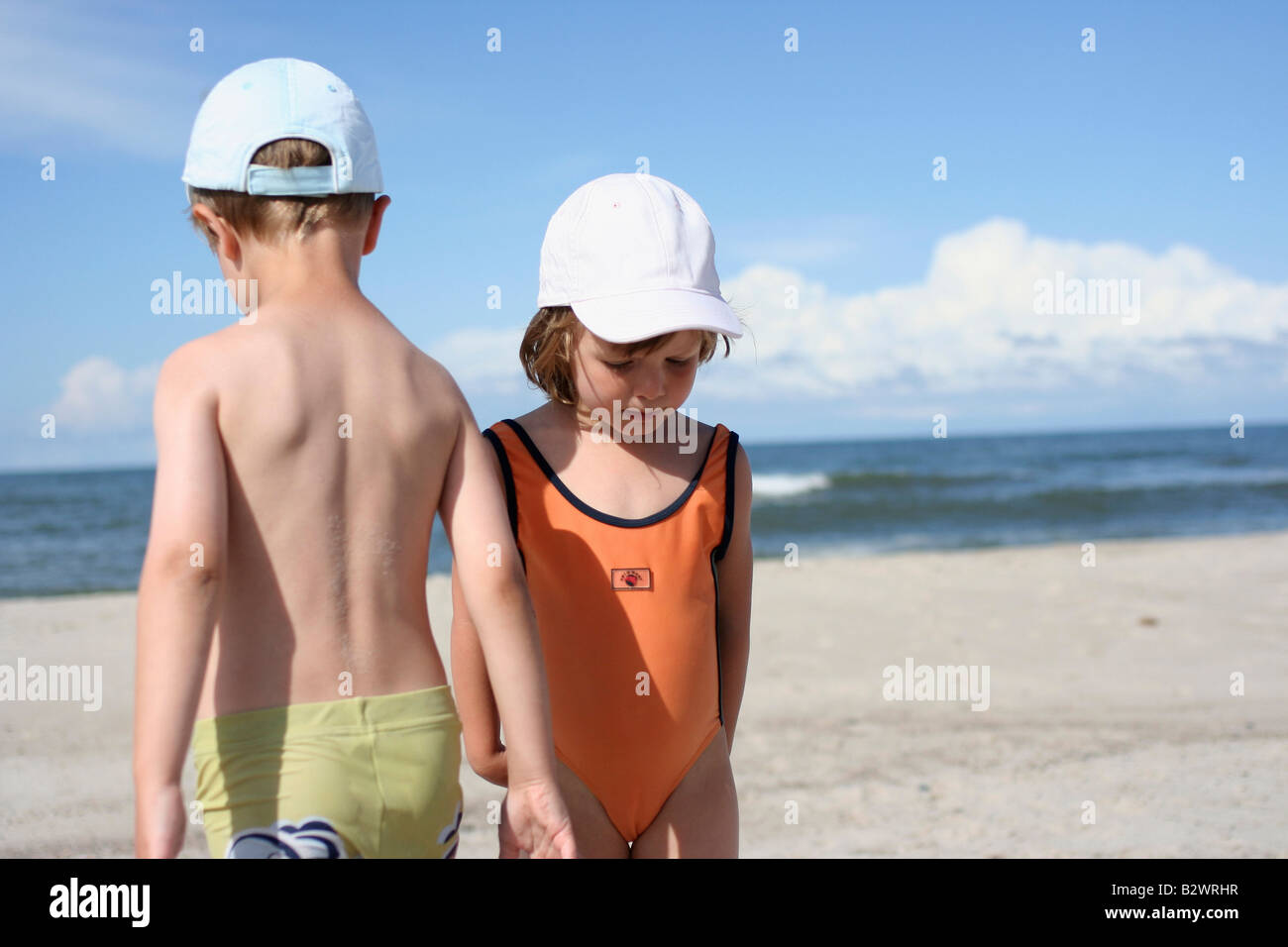 Girl and boy on a beach - Stock Image