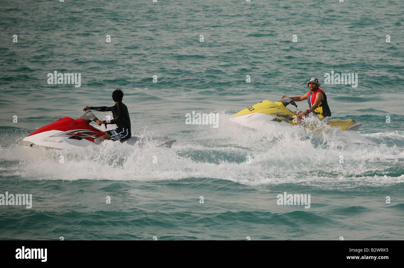 Jet skiers perform stunts in the Arabian sea along the corniche in Abu Dhabi - Stock Image