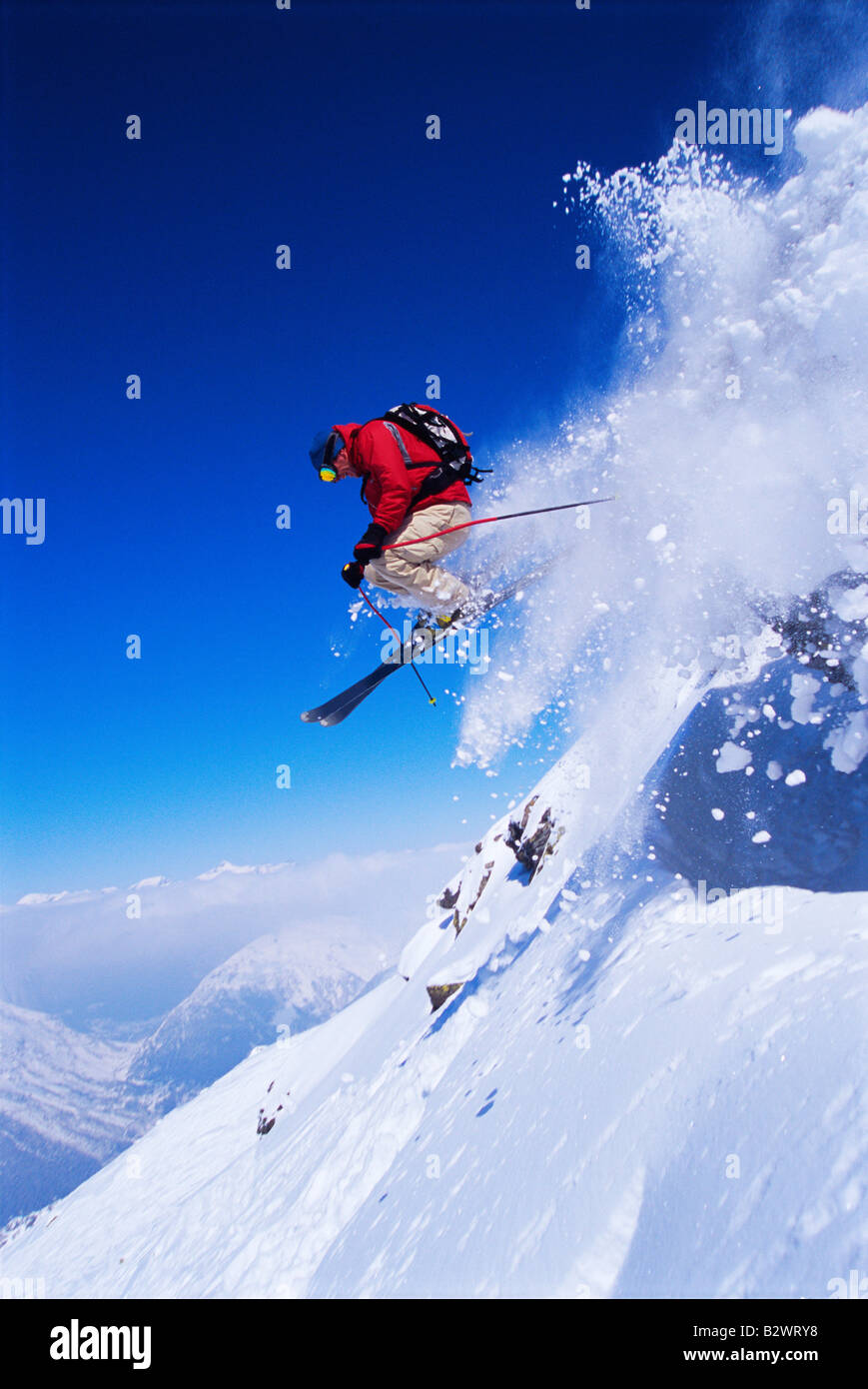 Skier jumping on snowy hill Stock Photo