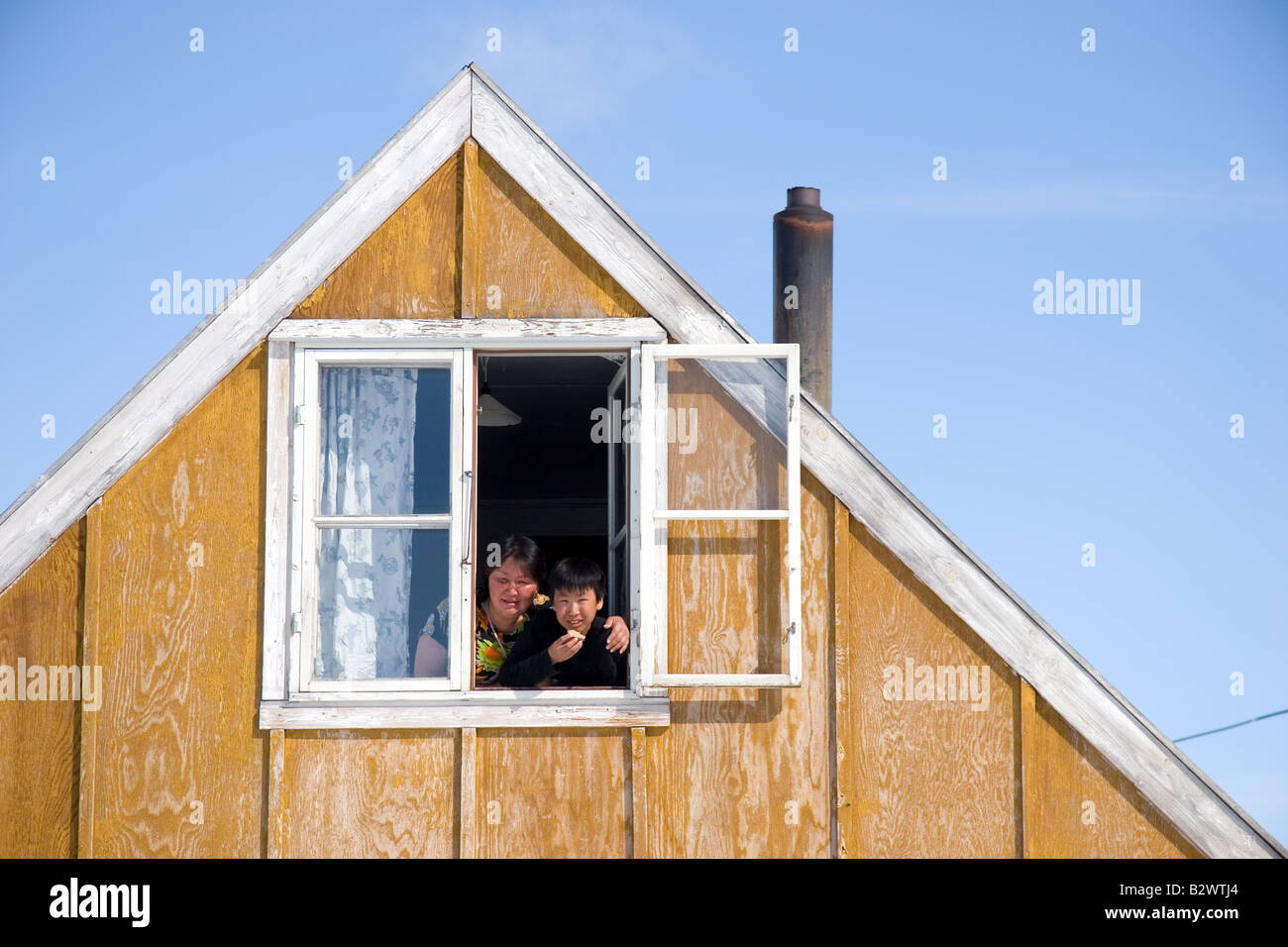Inuit family at the window of their traditional colourful house in the village of Ittoqqortoormiit, Scoresbysund, - Stock Image