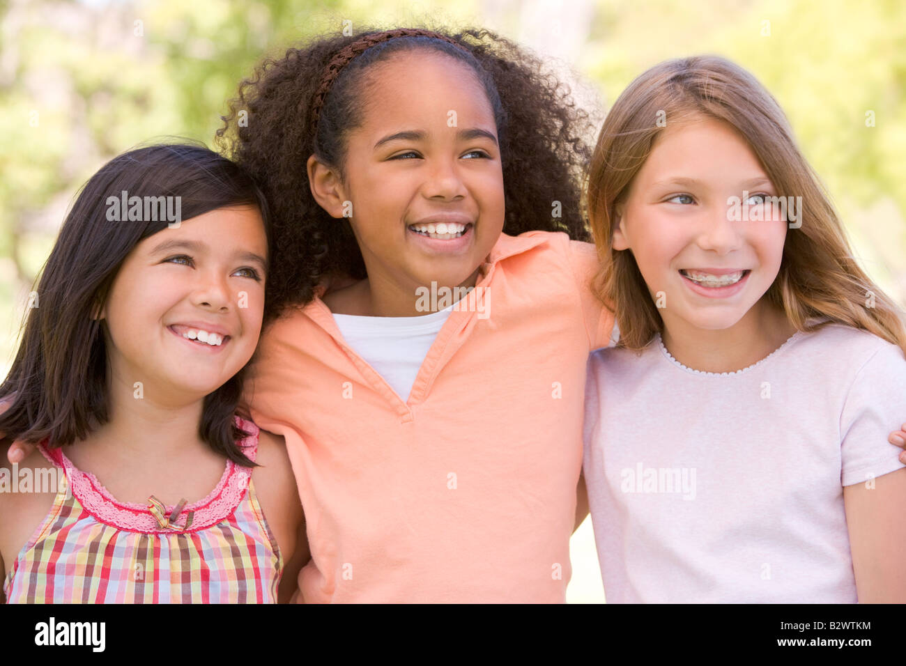 Three young girl friends outdoors smiling - Stock Image