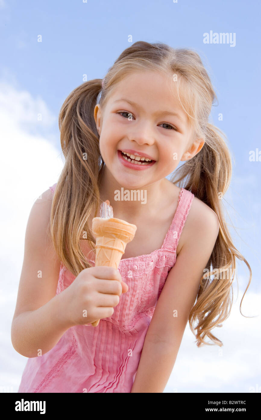 Young girl outdoors eating ice cream cone and smiling - Stock Image