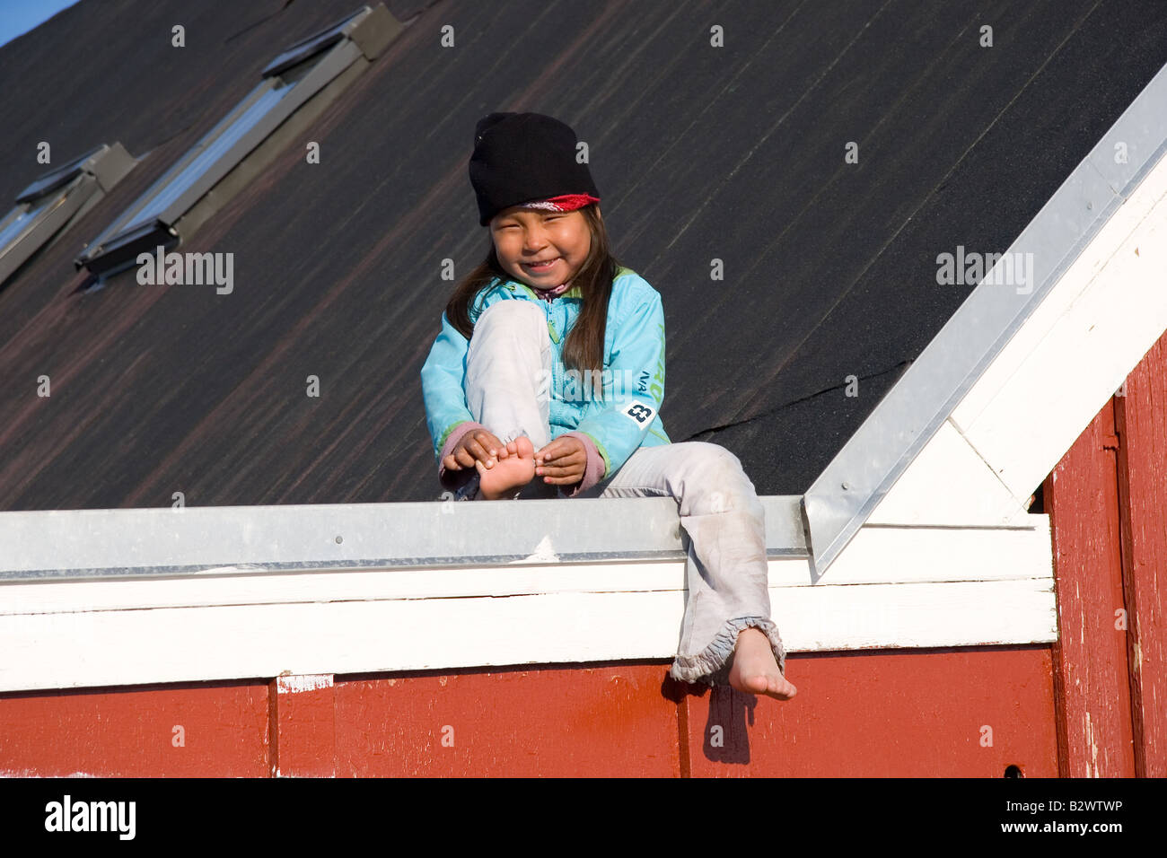A young Inuit girl plays on the post office roof in the village of Ittoqqortoormiit, Scoresbysund, East Greenland - Stock Image