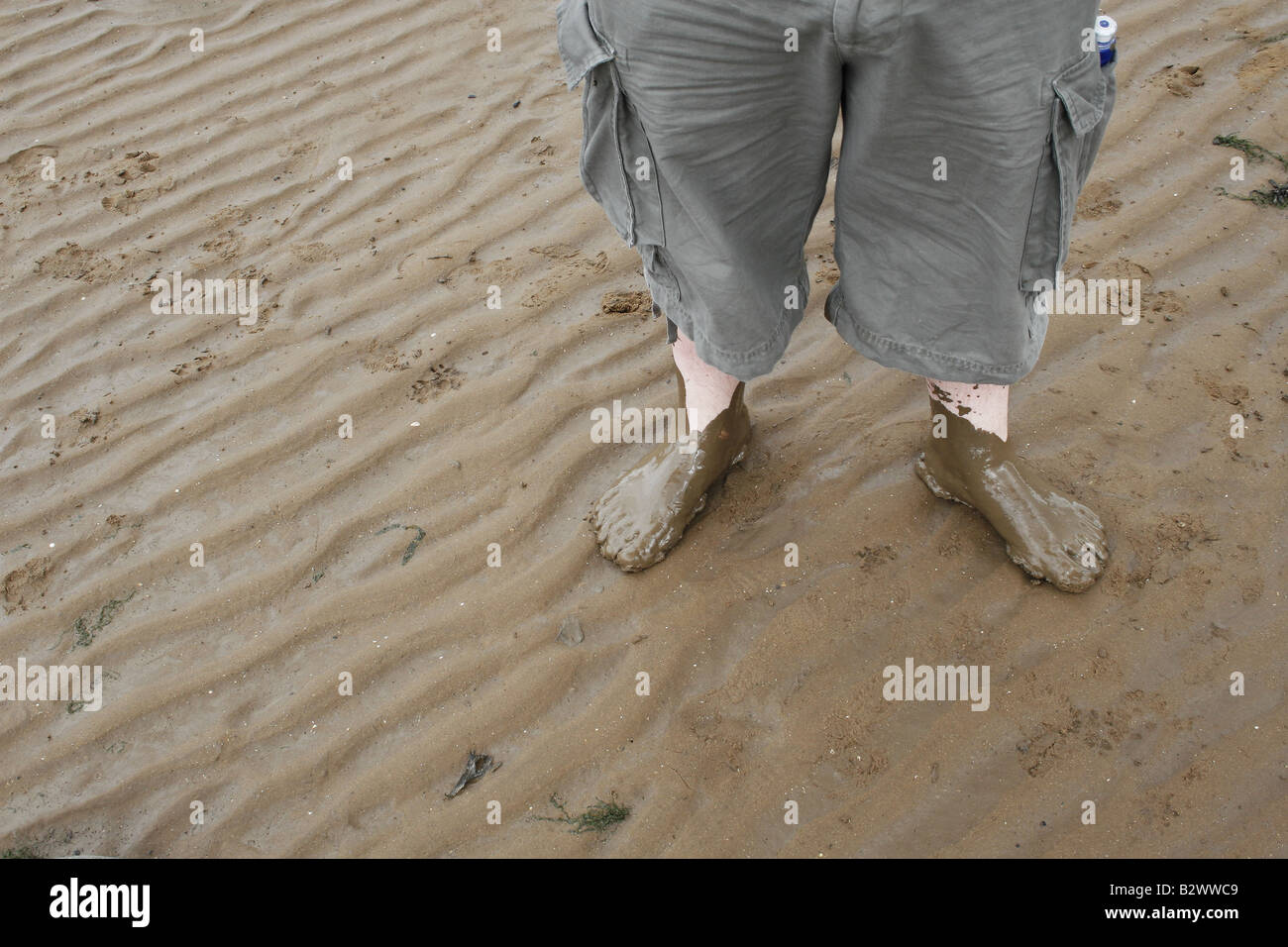 man s feet covered in wet sand Stock Photo