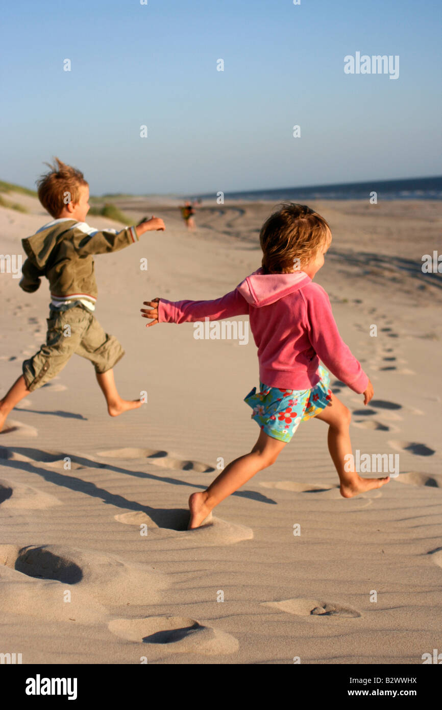 Children running on a beach - Stock Image