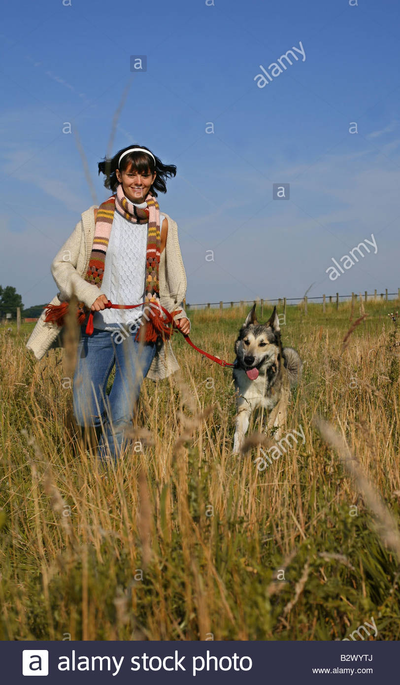 woman walking the dog in autumn landscape - Stock Image
