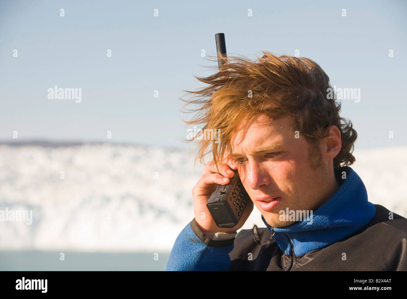 A Greenland tour guide using a satelite phone in a remote area at Camp Victor on Greenlands west coast - Stock Image