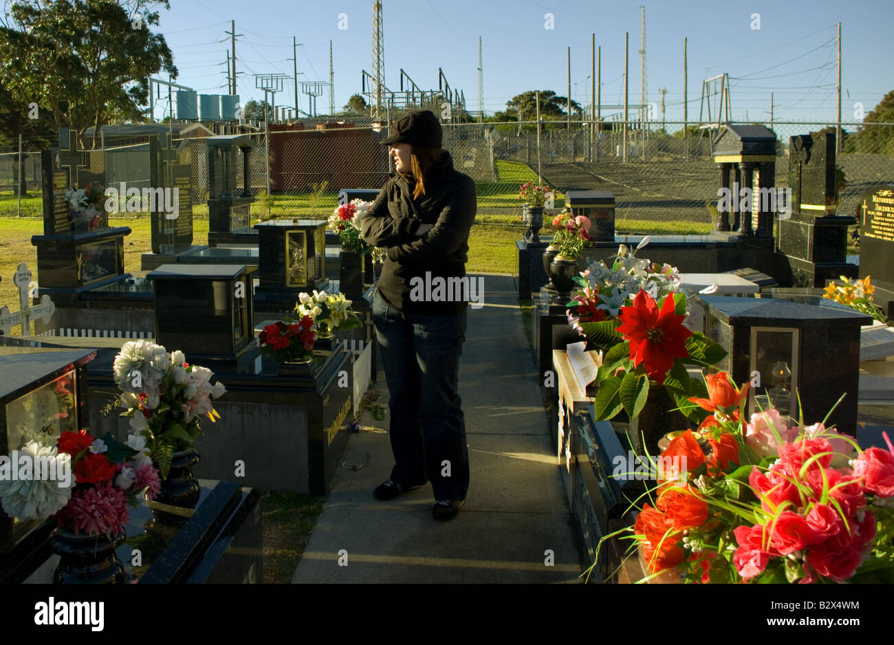 A woman walks through graves backed by powerlines. Stock Photo