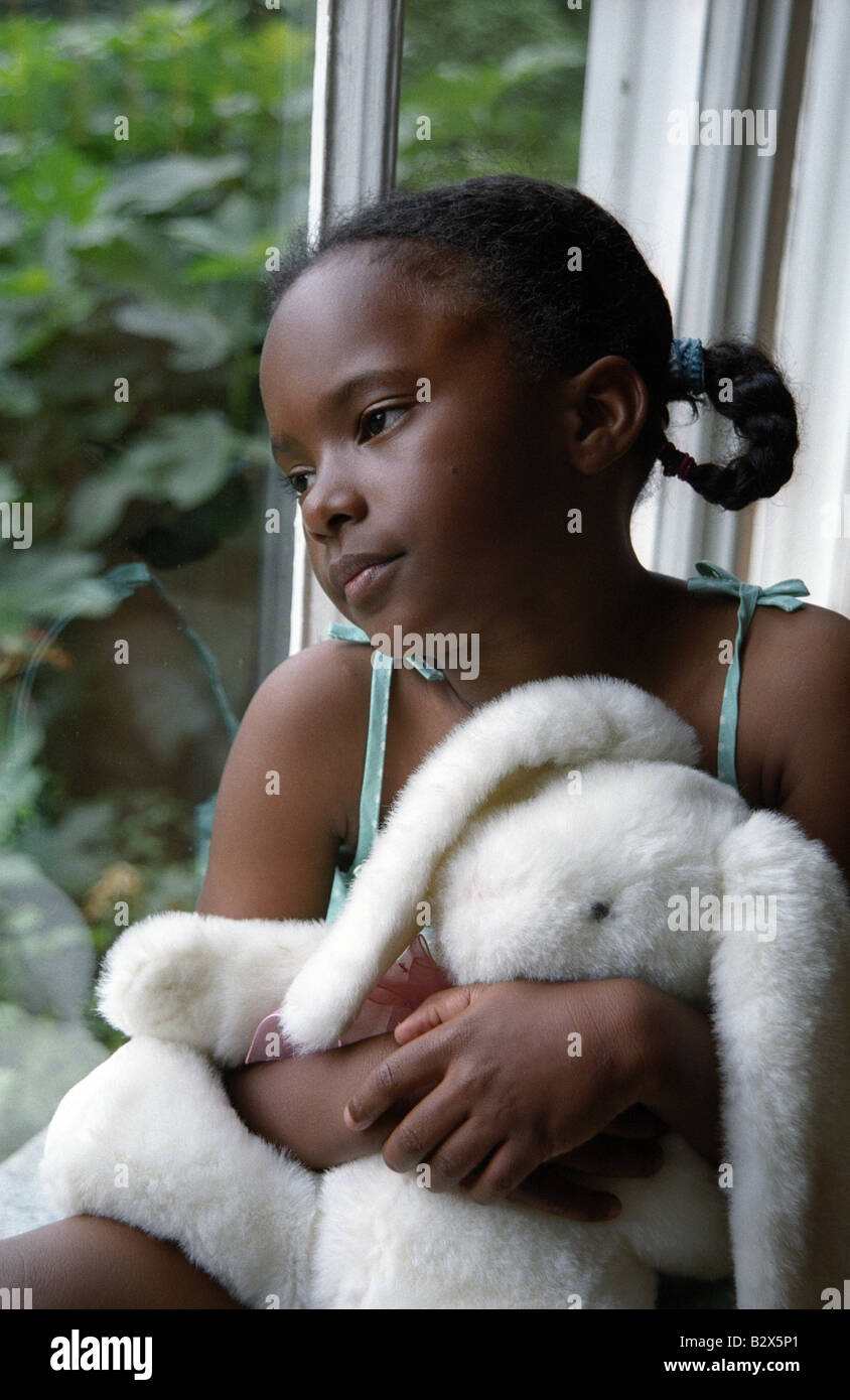 Sad Little Black Girl Looking Out A Window Stock Photo
