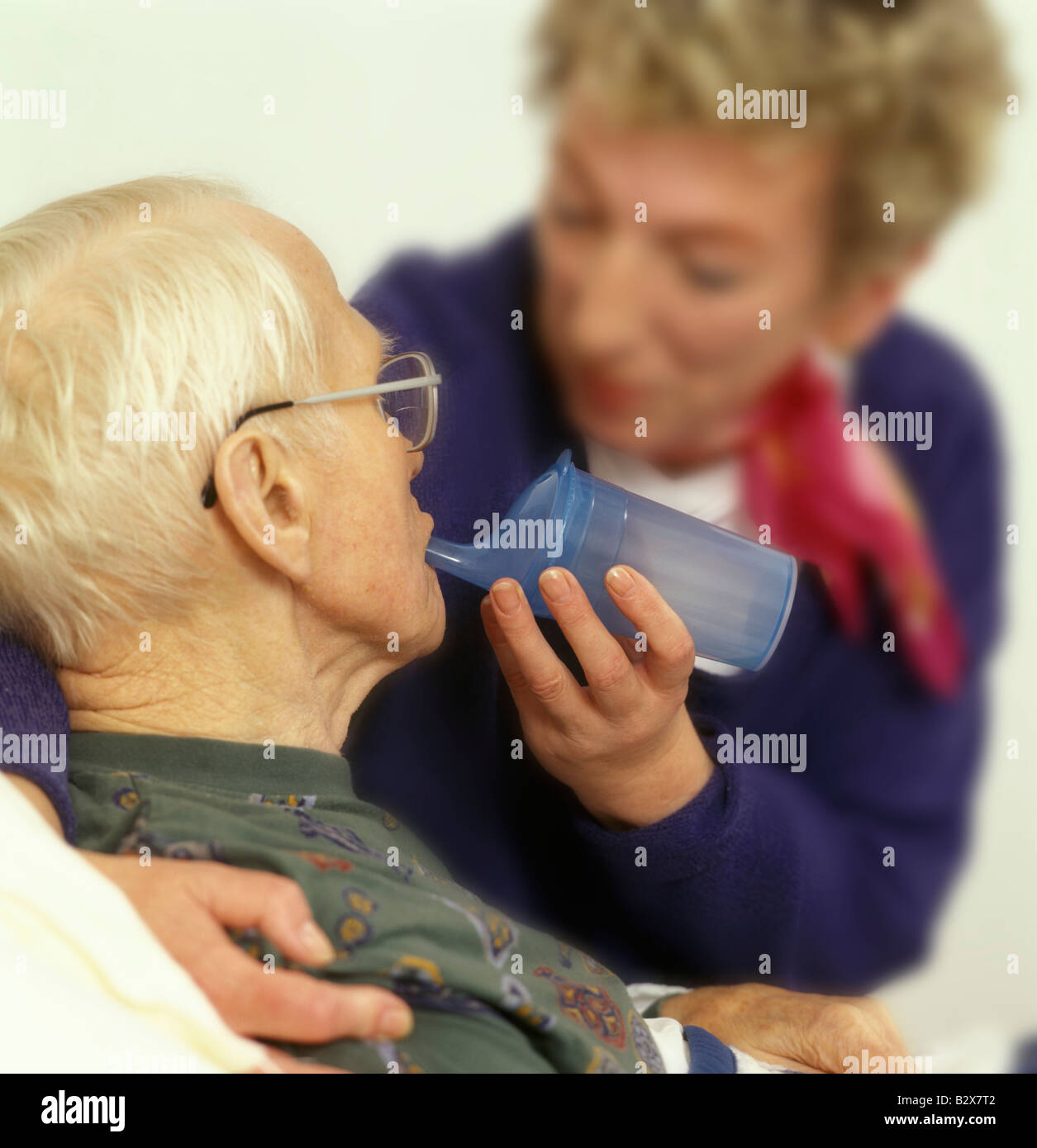 informal caregiver feeding an old in need of care man with a pap feeder - Stock Image