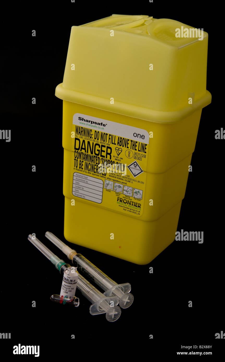 Hypodermic syringes beside a sharps box - Stock Image