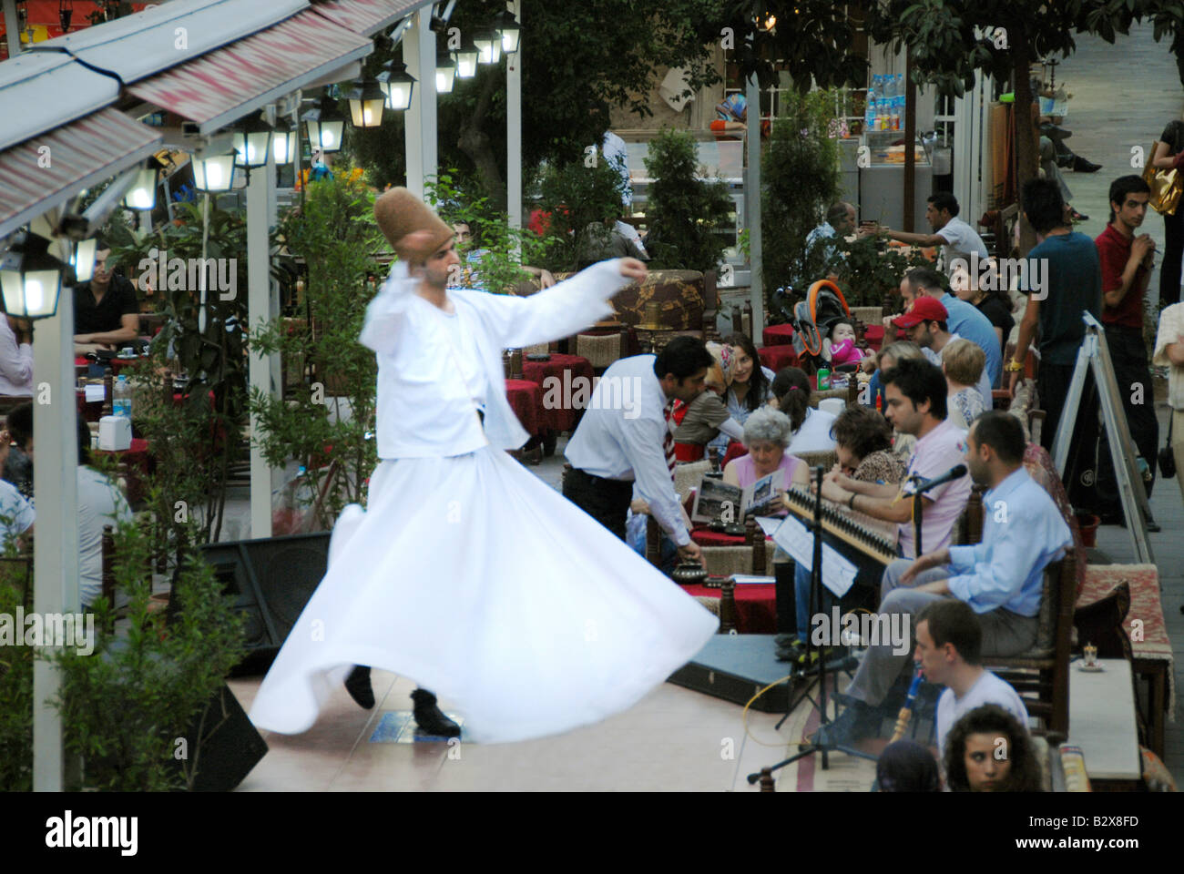 A Dervish dancer performing in a restaurant - Stock Image