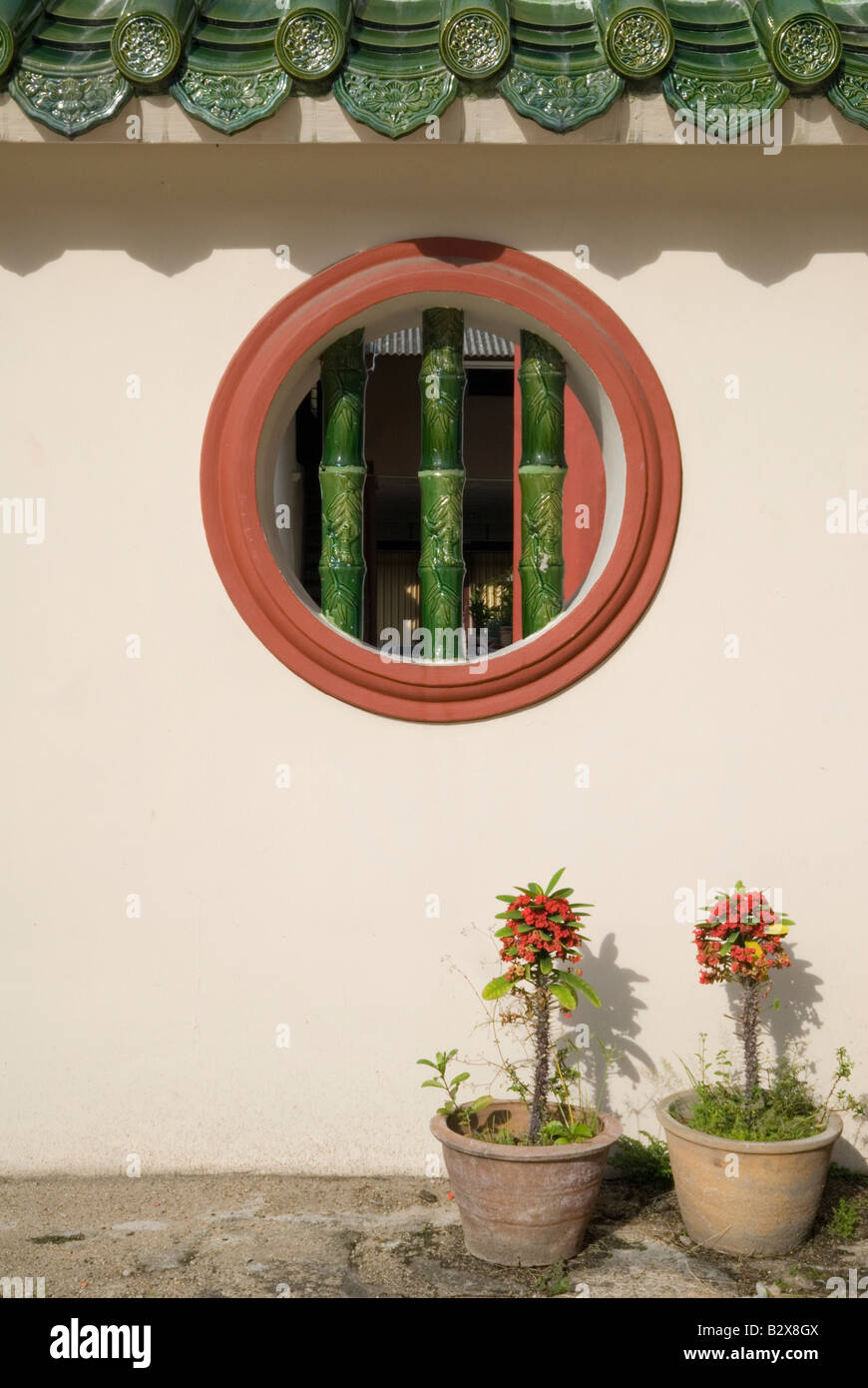 Courtyard pot plants and bamboo design round window in a wall at the ancestral straits Chinese clan temple, Cheah - Stock Image